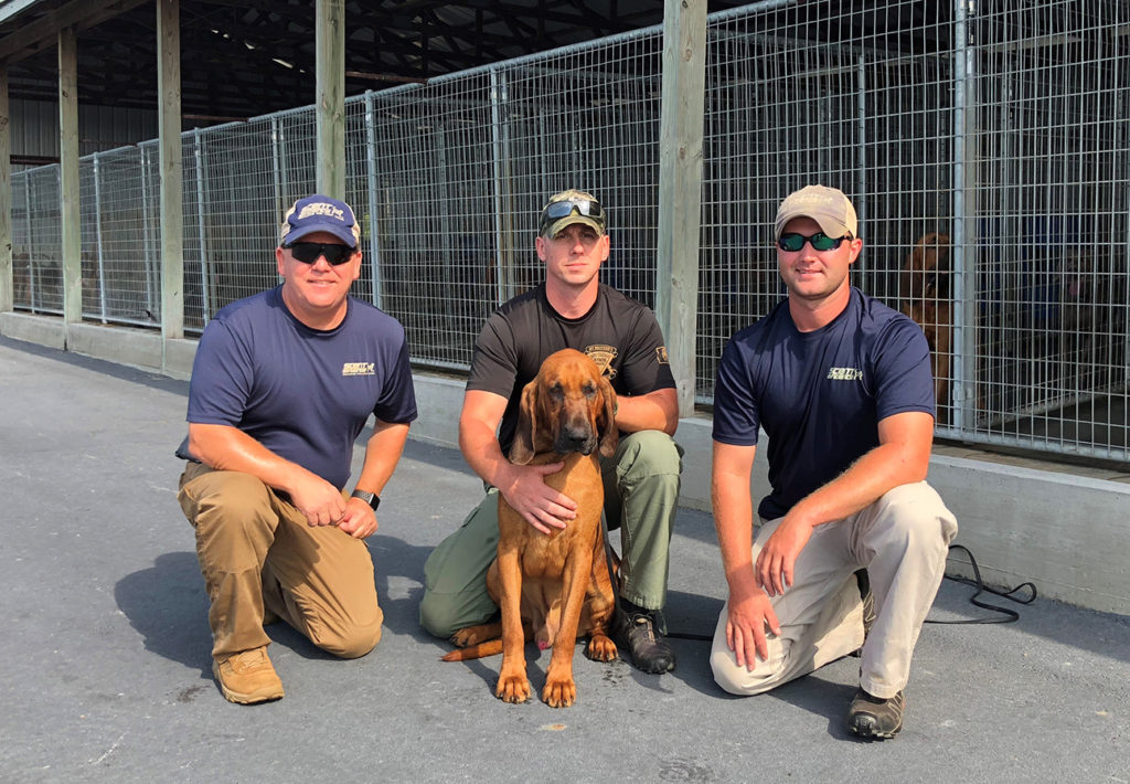 West Virginia State Police, Cpl. Patrick Jones and scent discriminate bloodhound, Shiloh, with SEK9 CEO, Paul Coley, and SEK9 Training Manager, Trey Cash